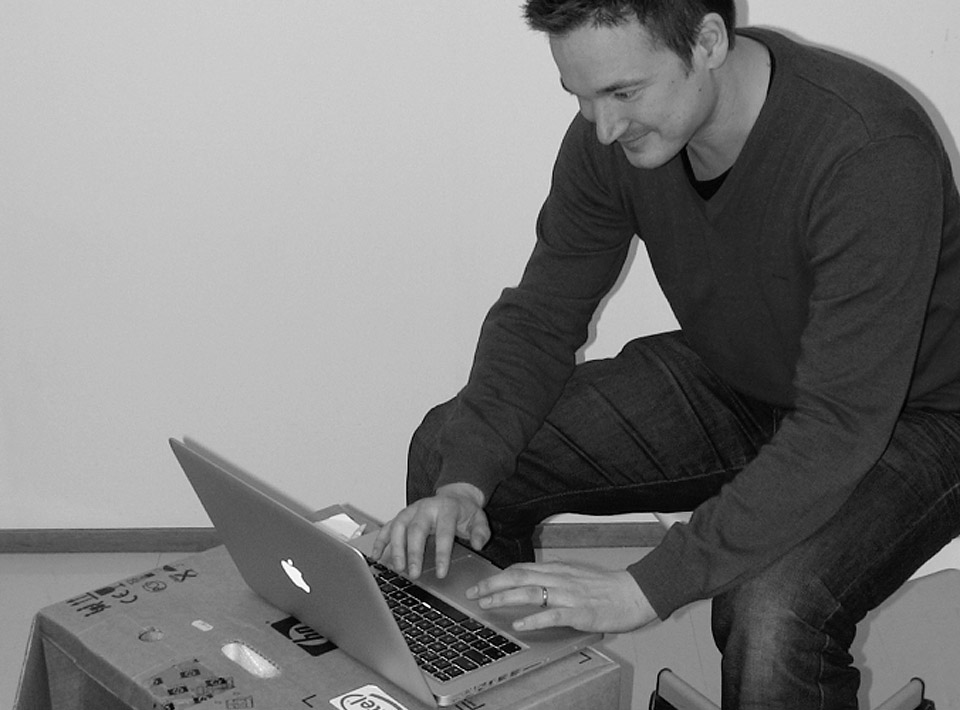 2010 Ilkka sitting at his cardboard desk at the Espoo office